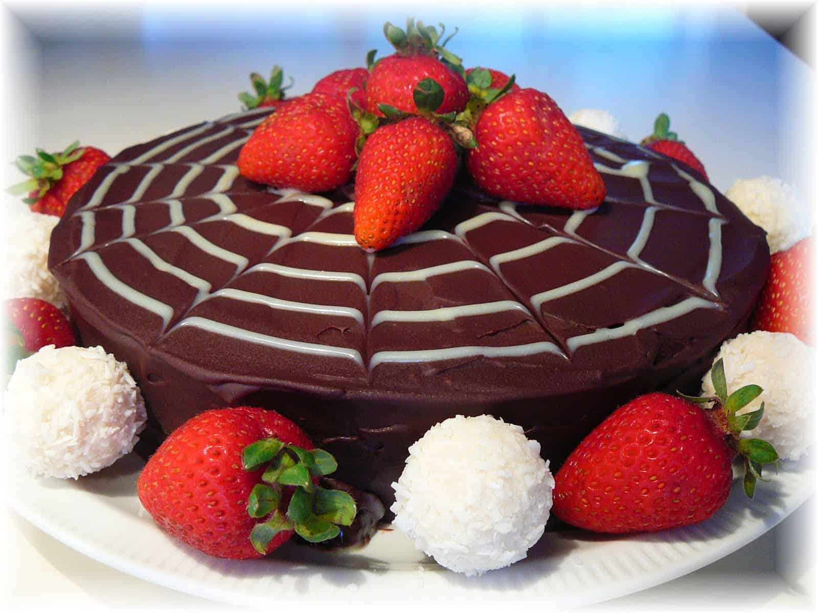 chocolate cake with white spider web design and strawberries on top