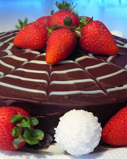 close up of chocolate cake with white spider web design and strawberries on top
