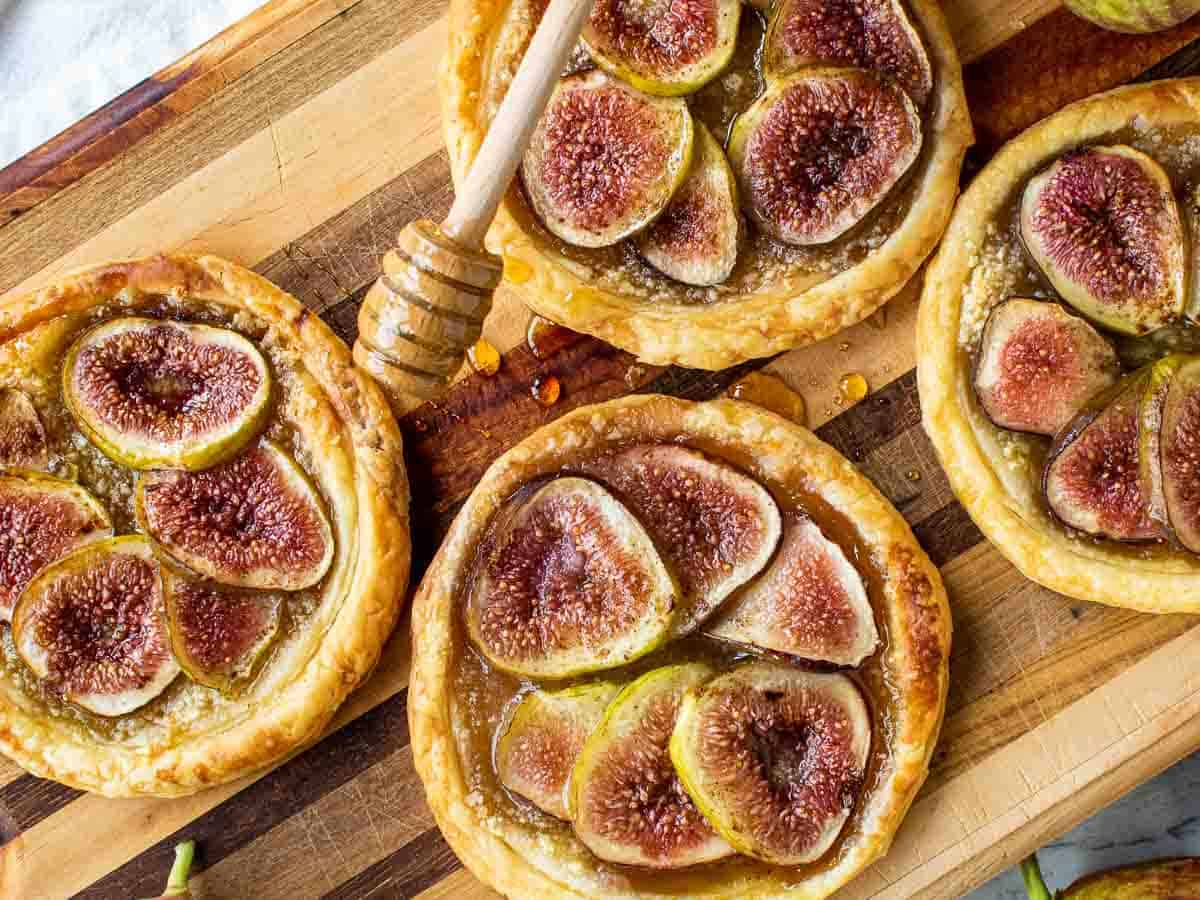 puff pastry fig tartlets on a wooden board with honey dipper drizzling honey over pastries viewed from above.