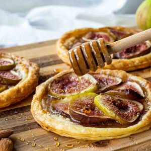 puff pastry fig tartlets on a wooden board with honey dipper drizzling honey over pastries.