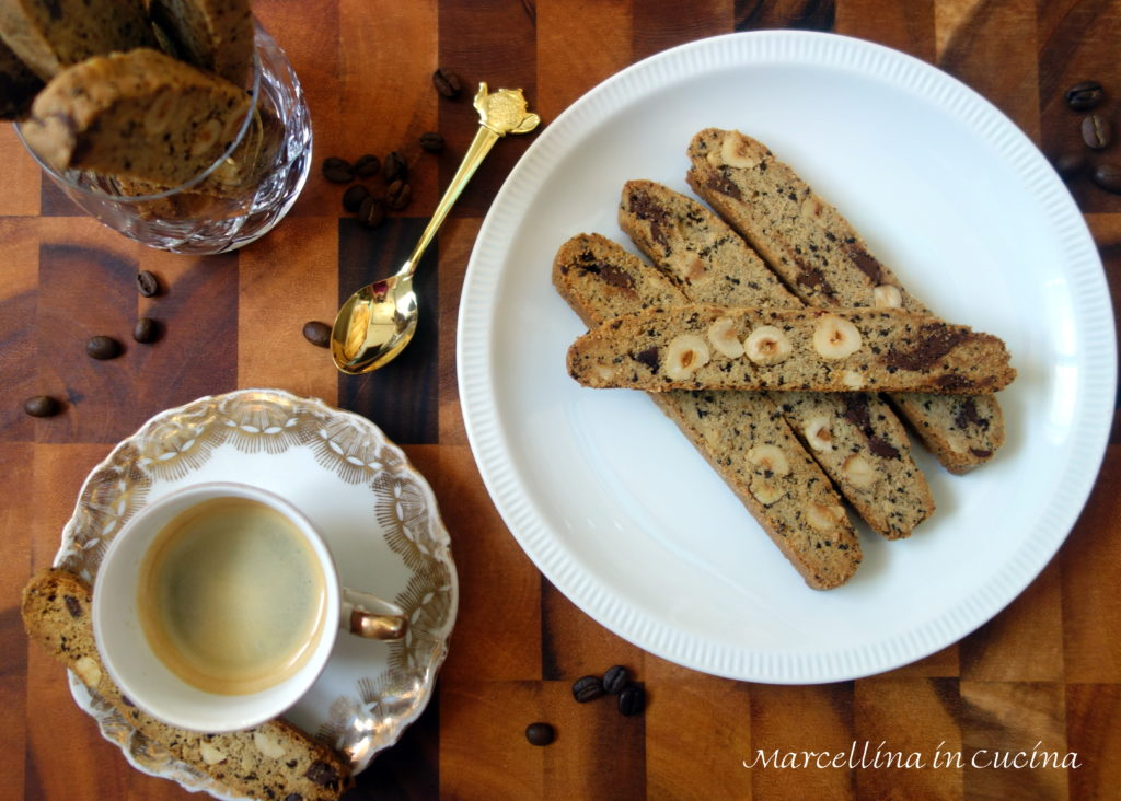 espresso hazelnut biscotti on white plate with gold spoon, espresso cup and coffee beans