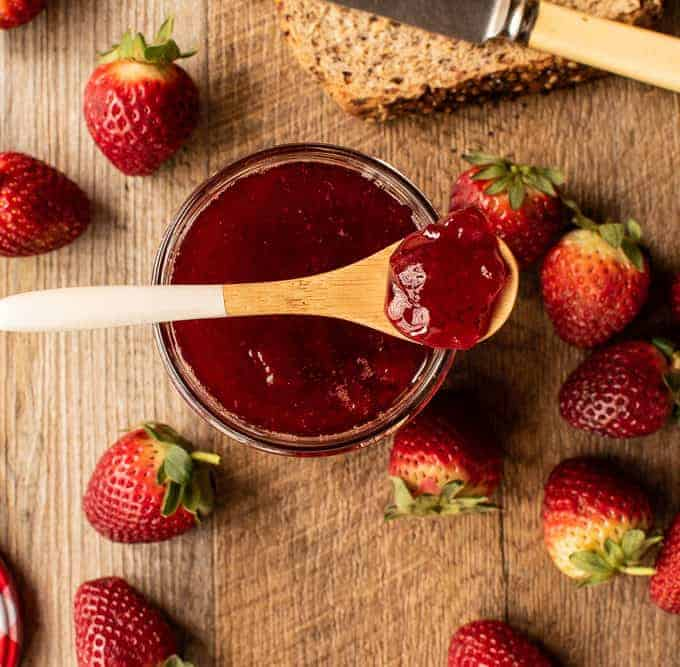 Jar of jam with strawberry jam on a spoon. strawberries and bread