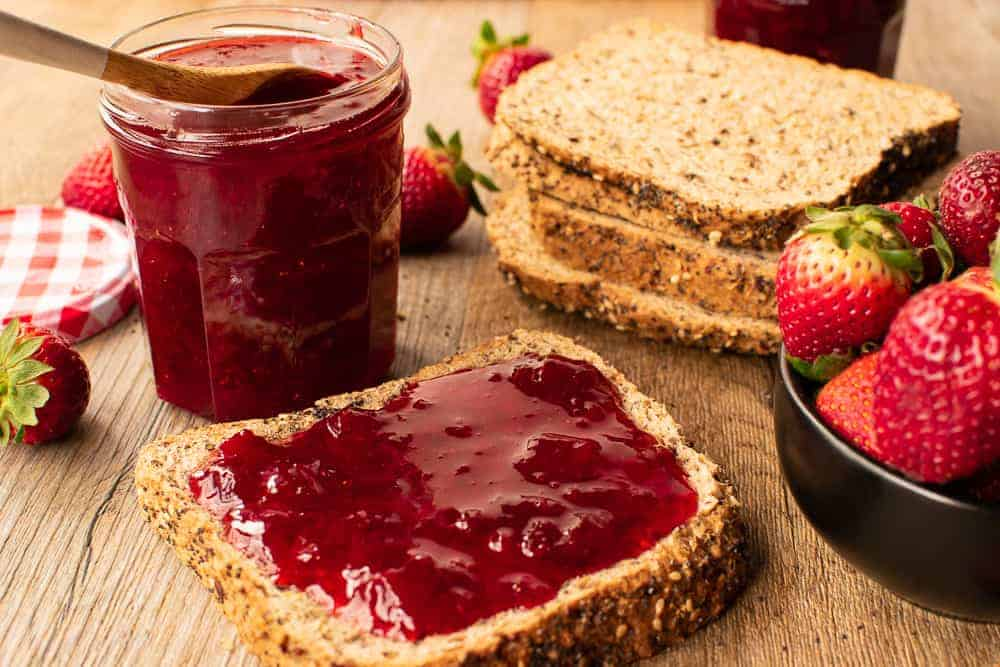 Strawberry preserves on bread with jam jar, bread and strawberries