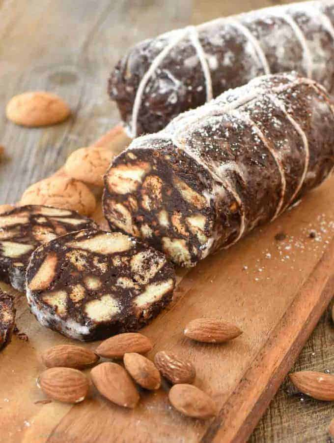 two chocolate salami on wooden board with three slices cut
