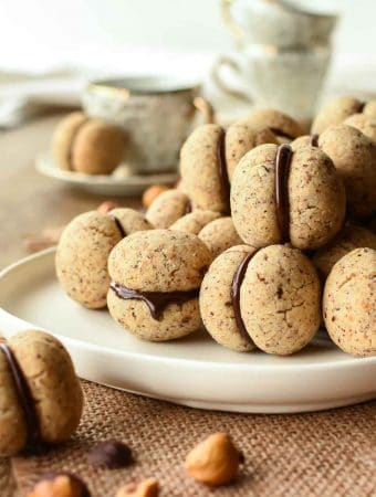 Pile of chocolate sandwiched hazelnut cookies on a white plate