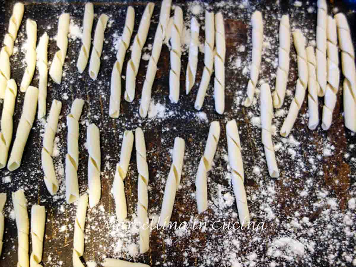 busiate pasta in a single layer on floured surface