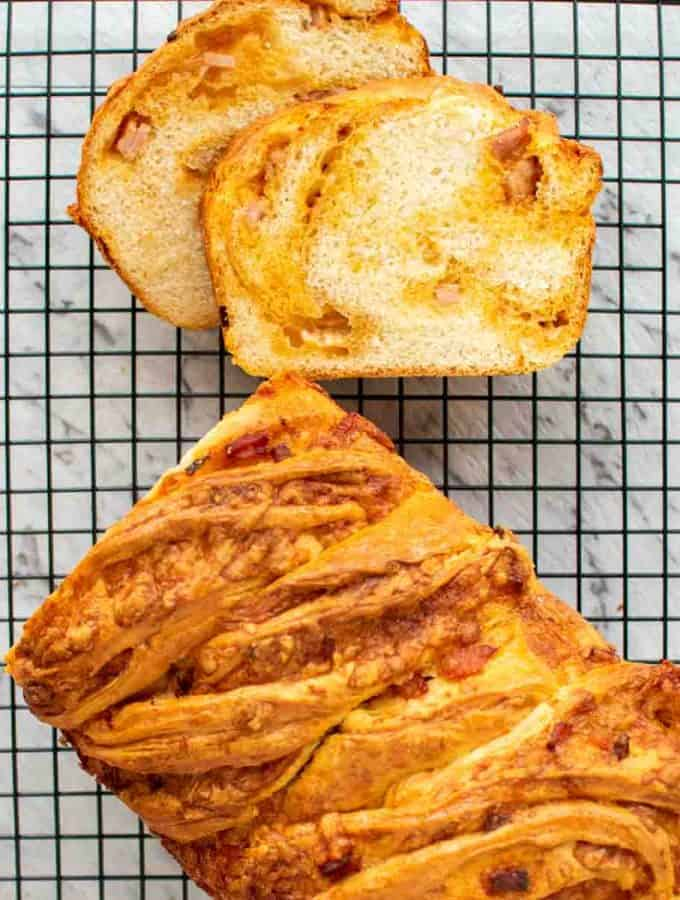 Bread loaf on black wire rack with two slices cut viewed from above