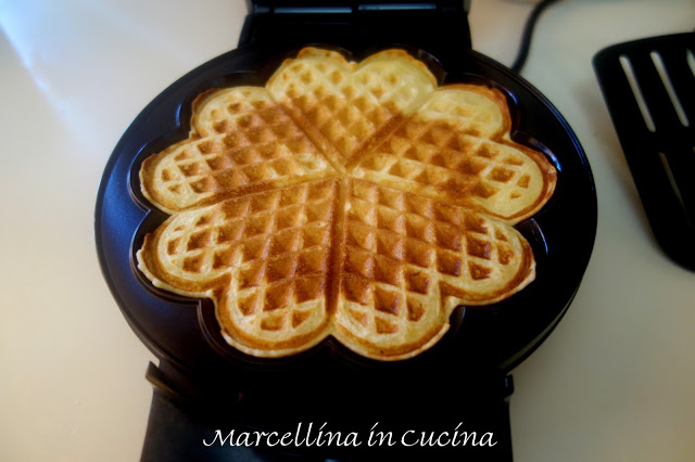 cooked waffle in black electric waffle iron viewed from the front
