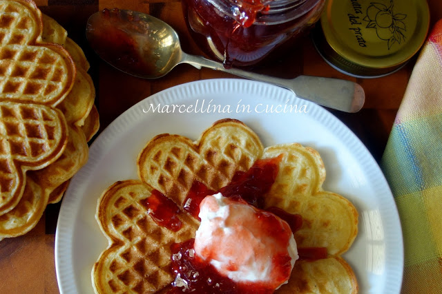 Viewed from above waffle on white plate with sour cream and strawberry jam