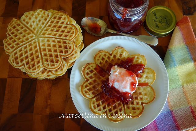 waffles on white plate topped with sour cream and strawberry jam, spoon, jam jar and stack of waffles on the side, viewed from above
