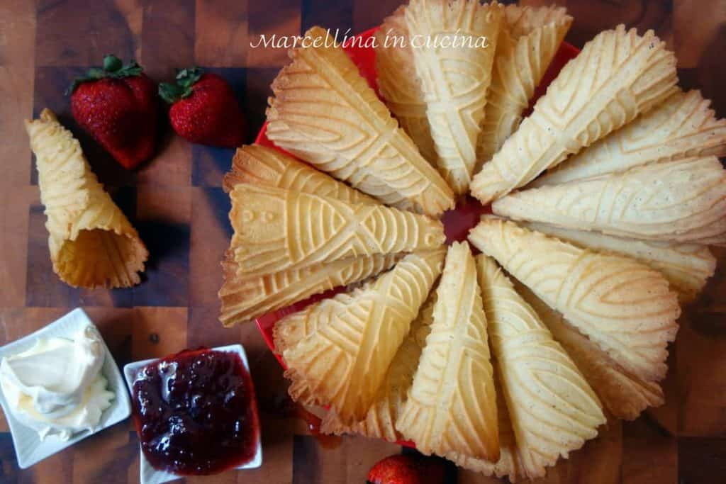 Krumkake cones arrange in a circle with jam and cream on the side