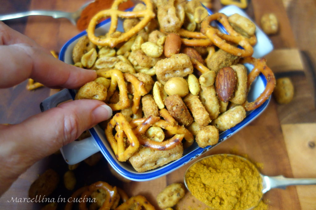 Picking up Spicy crunchy savoury snack of nuts, pretzels and crunchy cereal