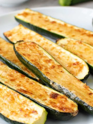 pile of cheese topped zucchini on a white plate.