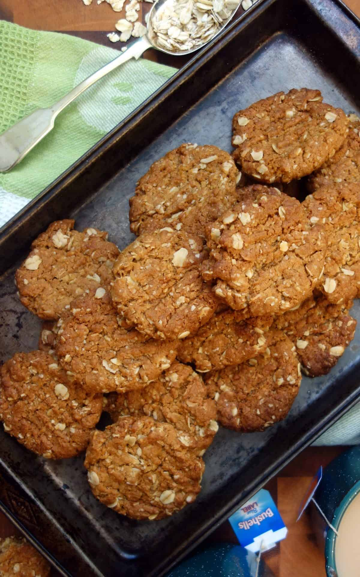 Overhead view of Anzac Biscuits in dark coloured baking tray