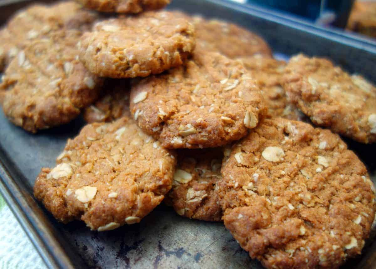 Close up of Anzac Biscuits on dark coloured baking tray