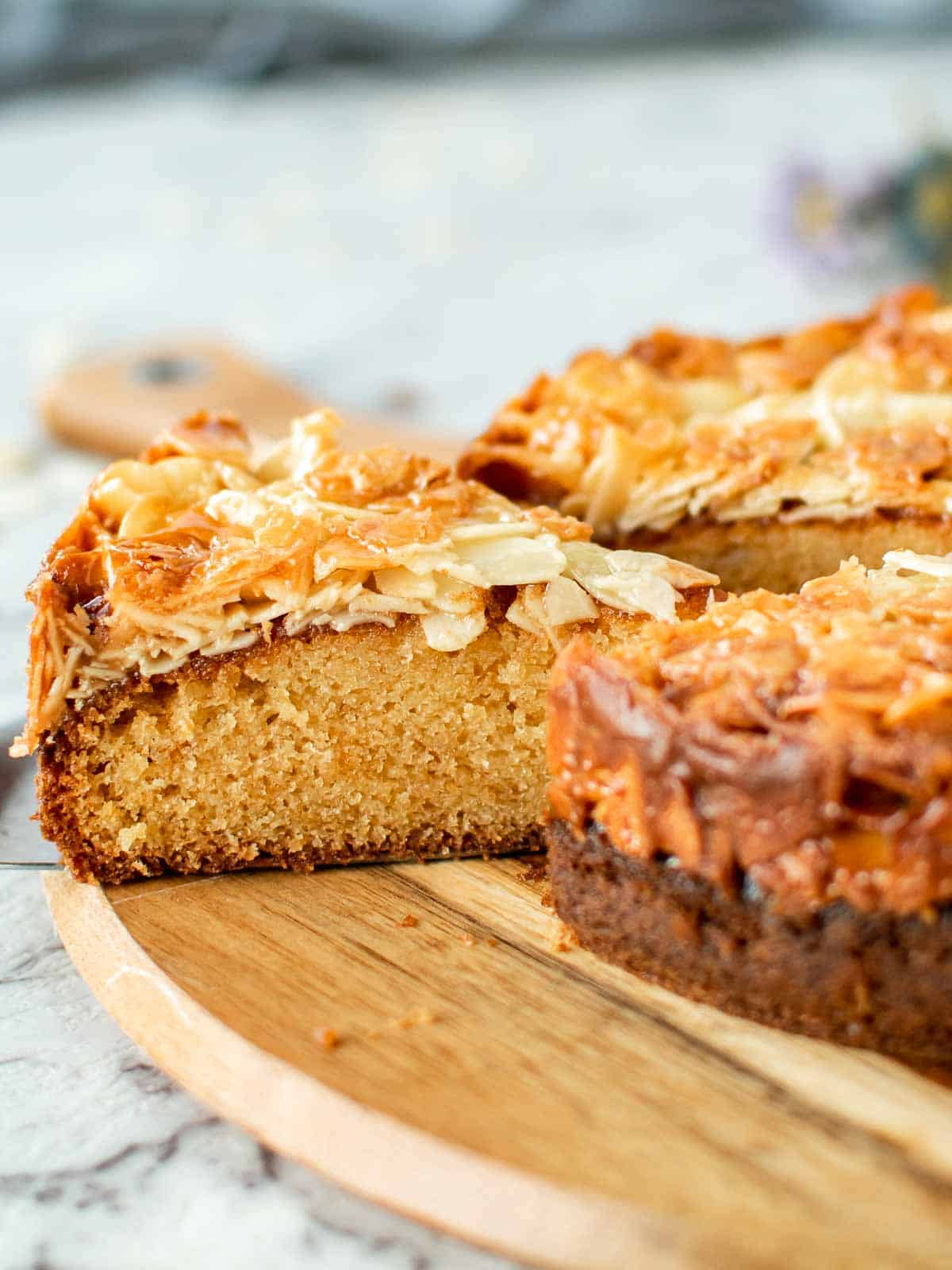 slice of cake with almond topping cut from whole cake viewed side on.