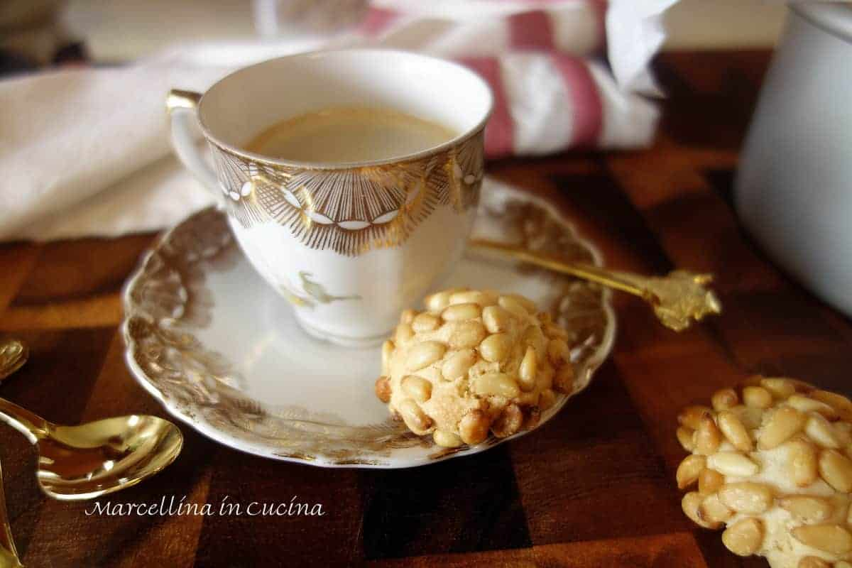 Pignoli cookies in cookie tin with espresso in vintage white and gold cup viewed from above.