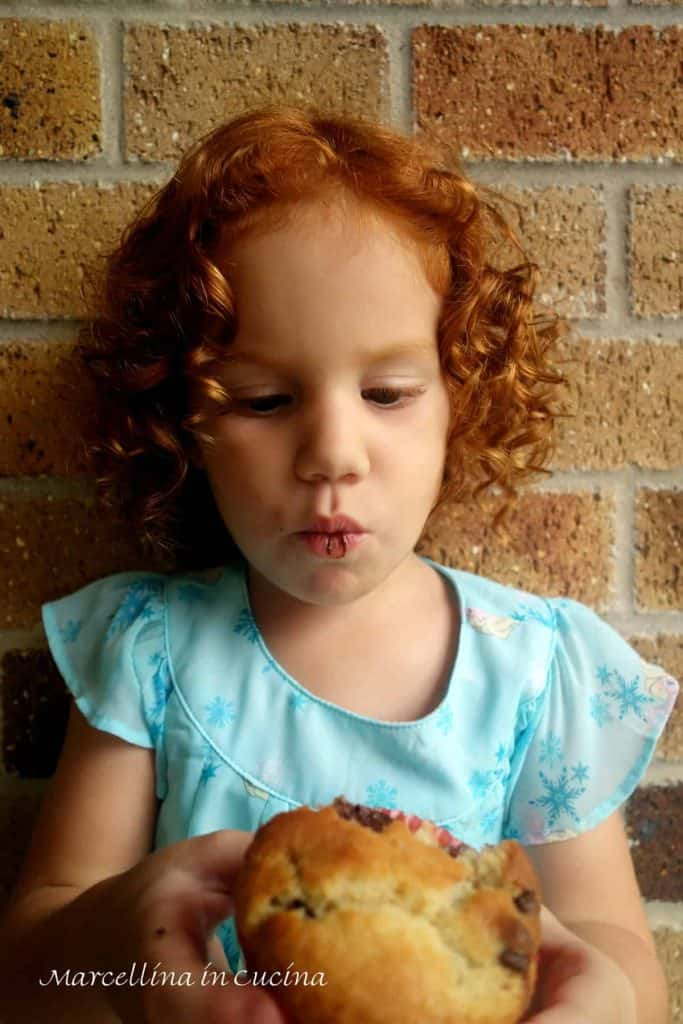 Red haired girl eating chocolate chip muffin