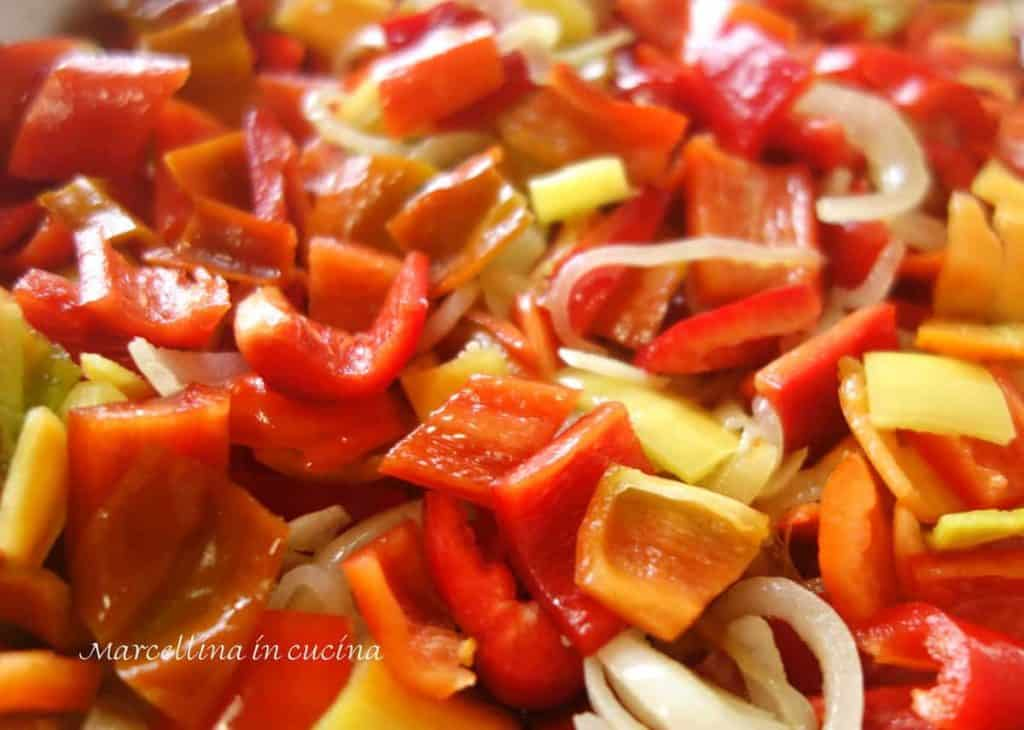 Red and yellow peppers and onions and garlic sauteing for peperonata