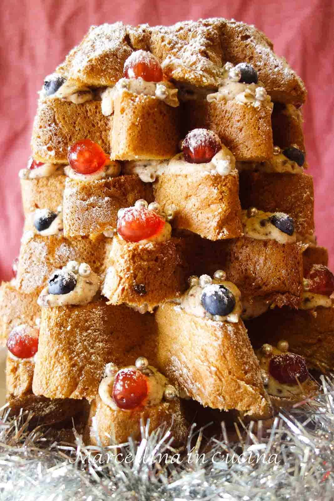 christmas tree cake with layers of cream filling, decorated with cherries and chocolate
