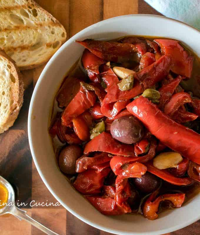 Sweet and Sour Peppers in a bowl with 2 slices of grilled bread and a spoon
