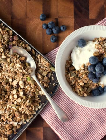 Tray of Granola with red and white cloth and bowl of granola, yogurt and blueberries