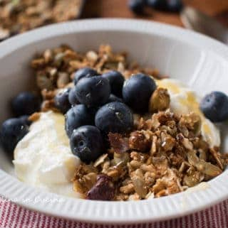 White bowl of homemade granola with yogurt and blueberries