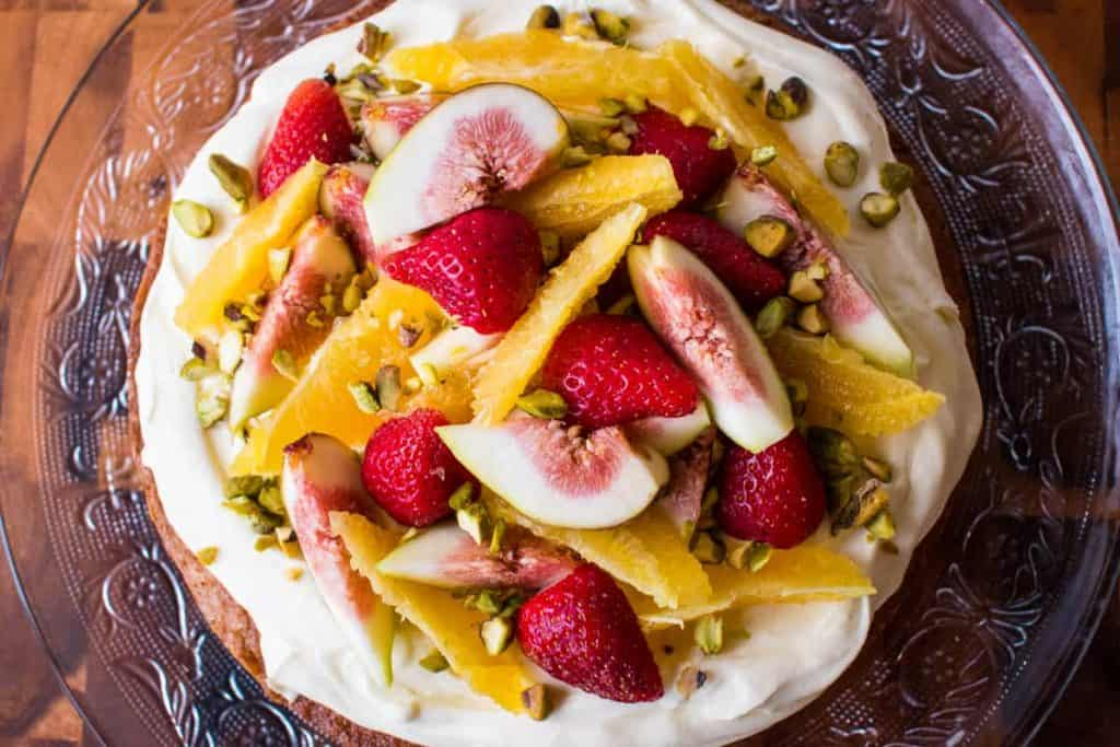 Top of Orange Syrup cake topped with orange segments, strawberries, figs and pistachios