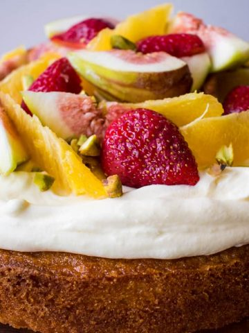 Orange Syrup cake topped with orange segments, strawberries, figs and pistachios