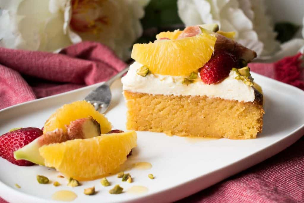 Slice of Orange Syrup cake topped with orange segments, strawberries, figs and pistachios