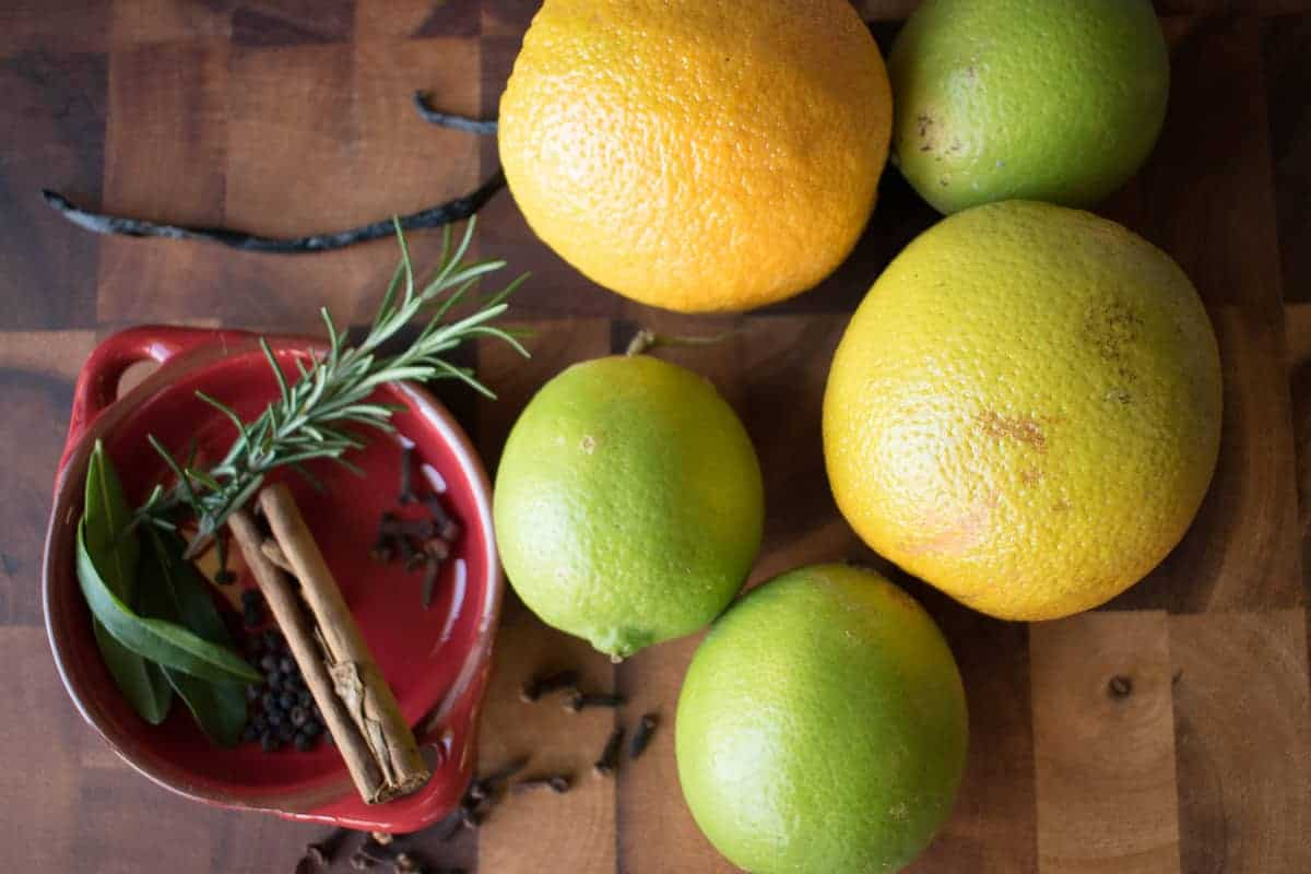 Two oranges, two limes, one cinnamon stick, rosemary, cloves and peppercorns.