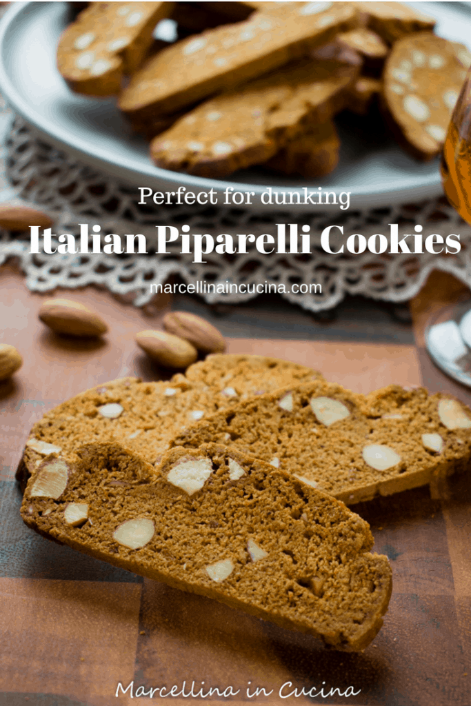 Pinterest image of Italian Piparelli, spicy biscotti on wooden table with glass of liqueur and plate of biscotti in the background