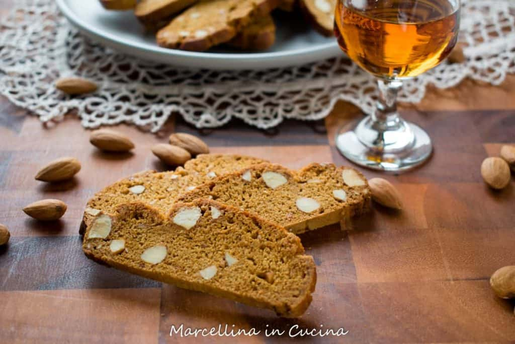 Italian Piparelli, spicy biscotti on wooden table with glass of liqueur and plate of biscotti in the background