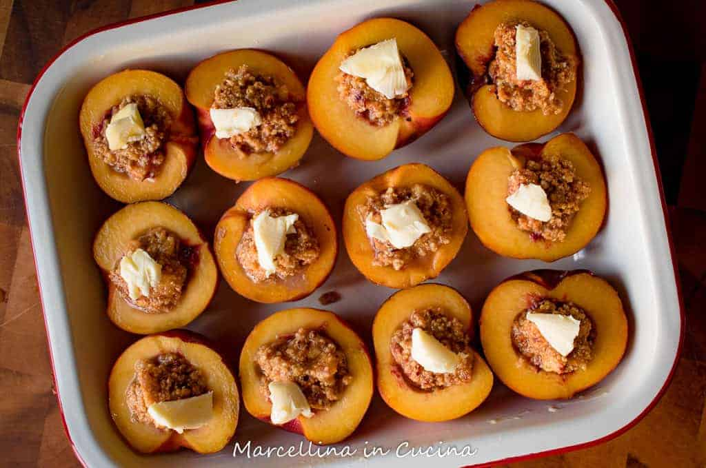 Peaches stuffed with amaretti and topped with knob of butter ready for baking