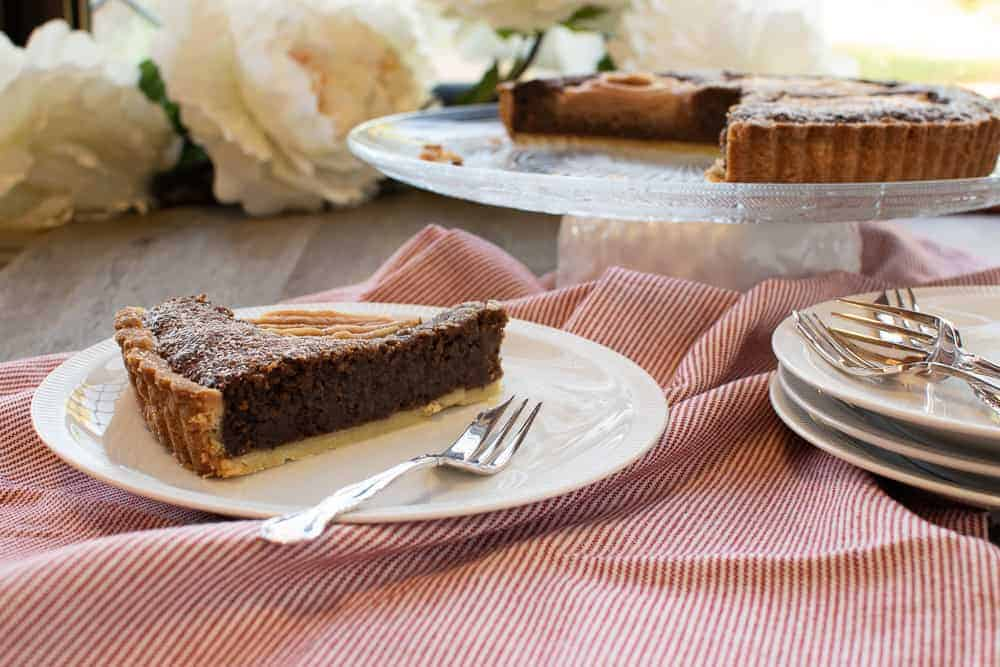 Slice of Chocolate, Hazelnut and Pear Tart with whole tart in background