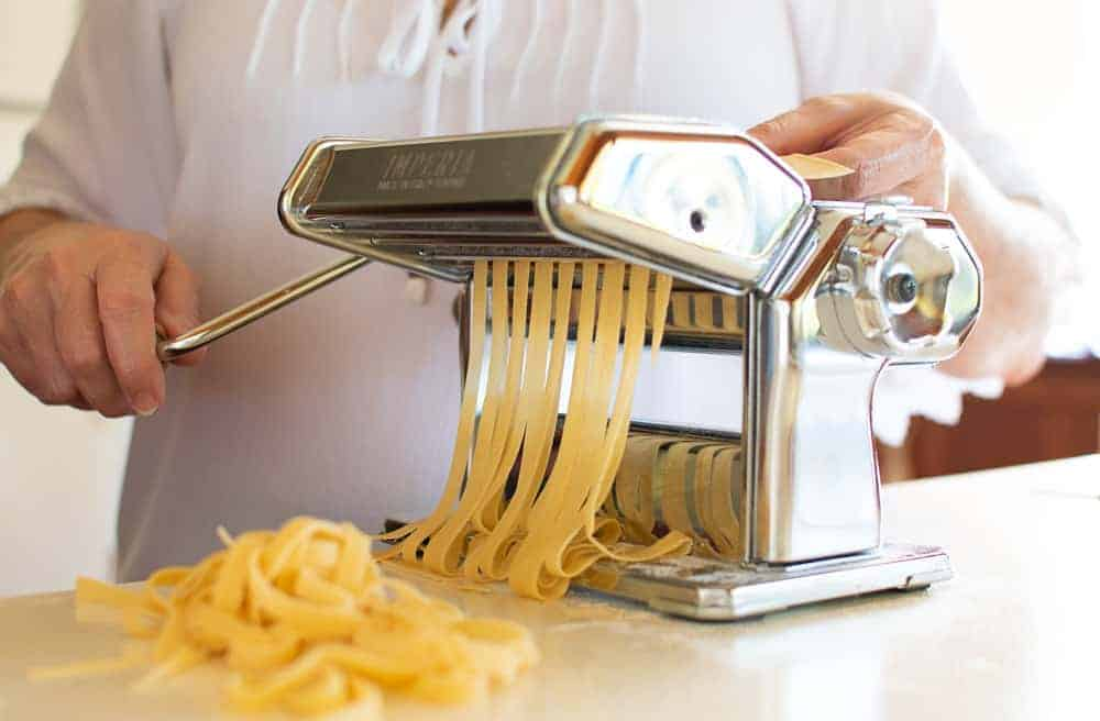 woman in white using a pasta machine to cut pasta sheets into fettuccine