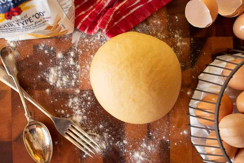 Pasta dough with eggs, egg shells, flour, towel, fork and spoon