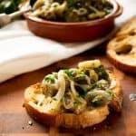 Oregano Marinated eggplant on bread with dish full of marinated eggplant, parsley and bread in the background
