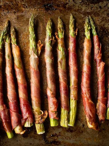 Prosciutto wrapped asparagus on rustic metal pan.