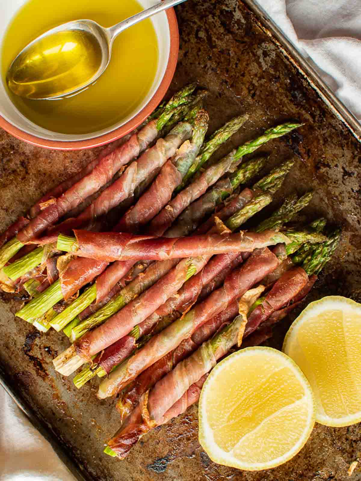 Prosciutto wrapped asparagus with lemon cheeks and olive oil in a red and white dish viewed from above.