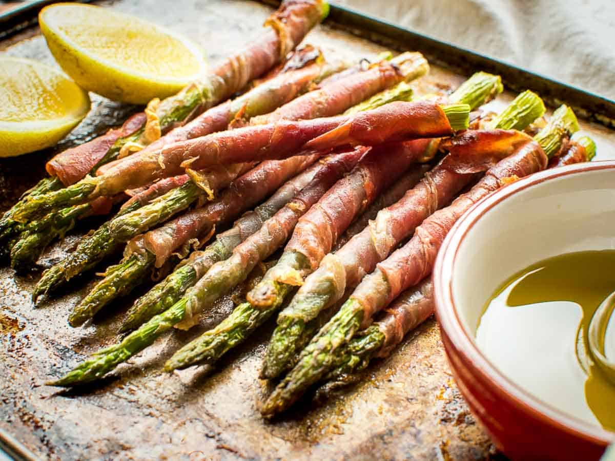 Prosciutto wrapped asparagus with lemon cheeks and olive oil in a red and white dish.