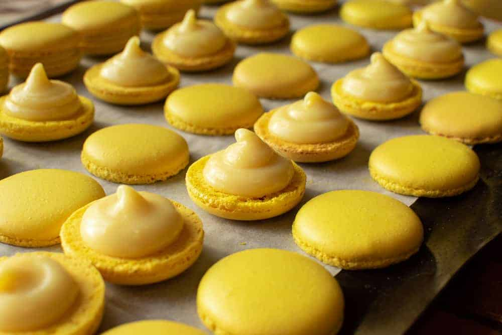Yellow macarons halves topped with lemon filling