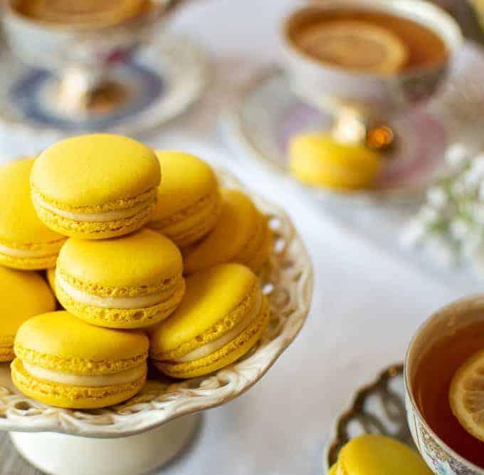 Lemon Macarons on white stand with three cups of lemon tea on a white cloth
