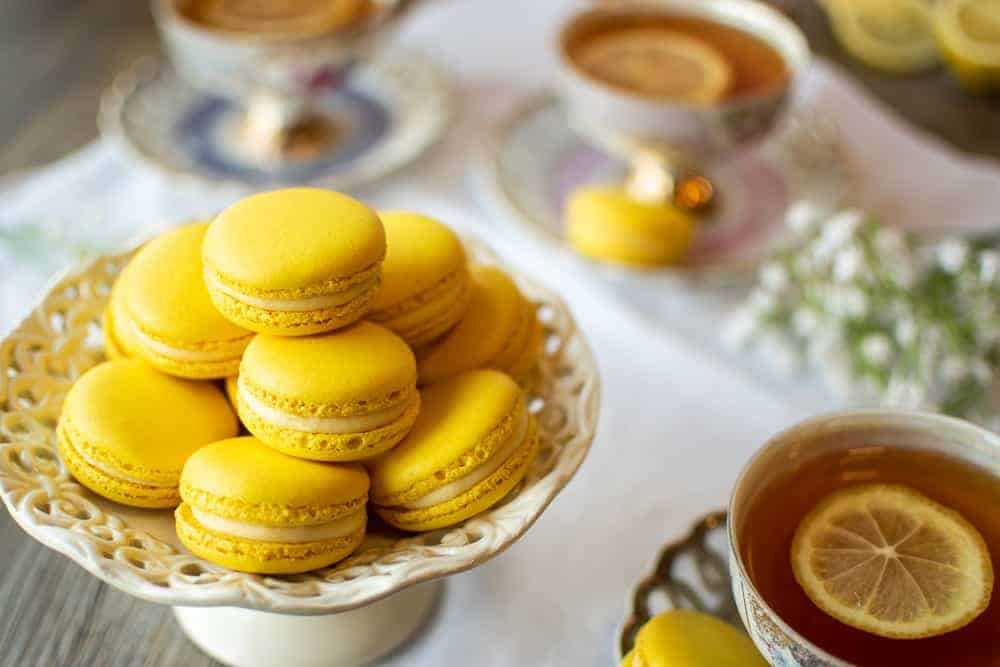 Lemon Macarons on white stand with three cups of lemon tea on a white cloth