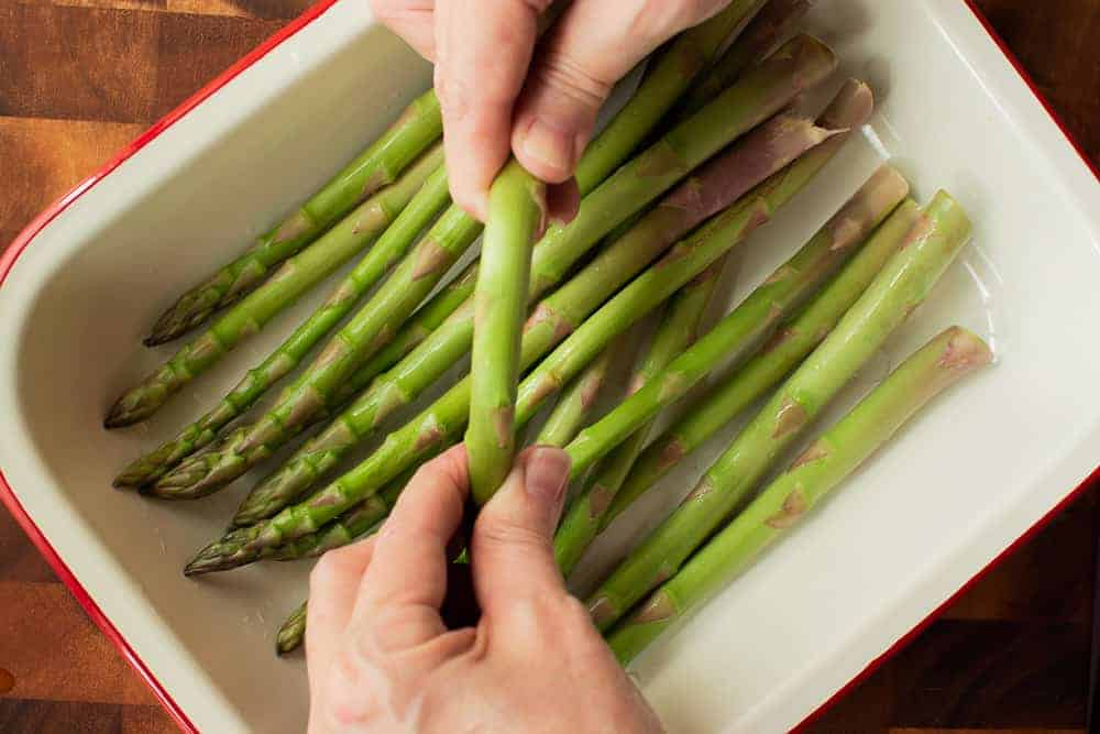 Pile of green asparagus in white pan and hands snapping ends of asparagus off