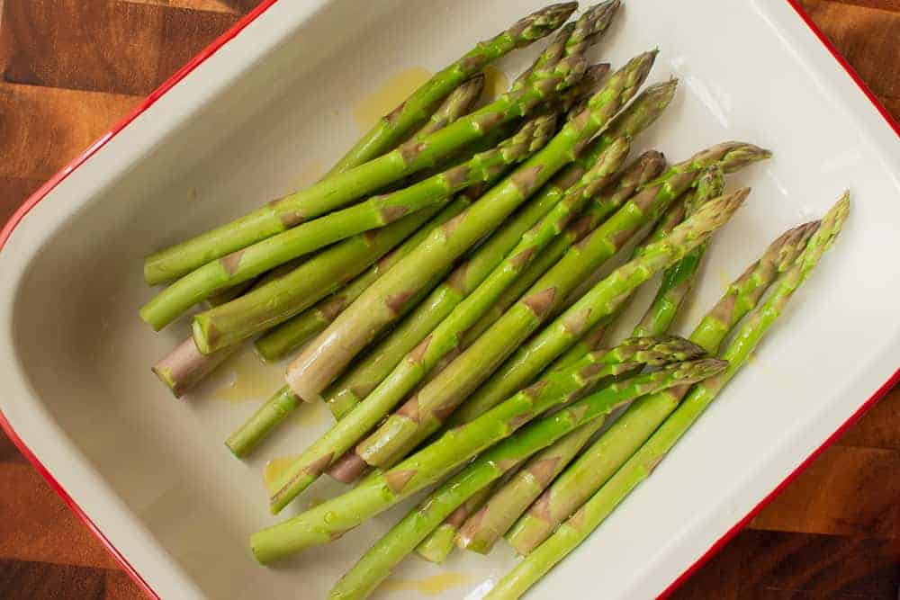 Olive oil coated green asparagus in red trimmed white pan