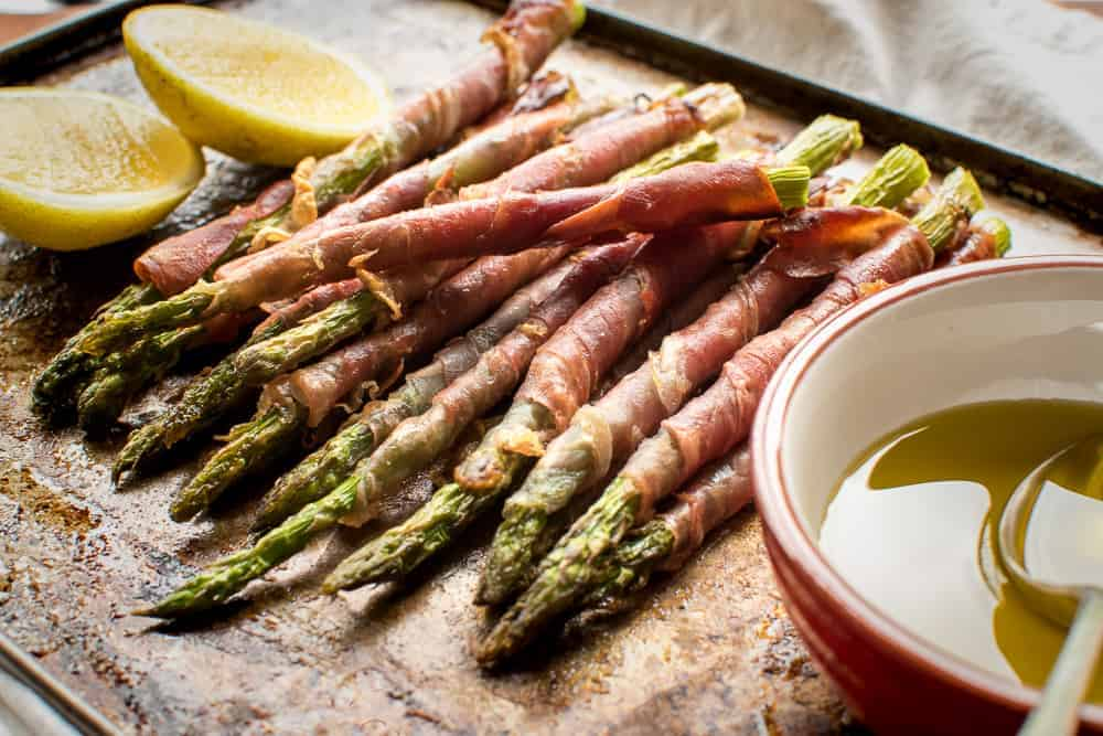 Prosciutto wrapped asparagus with lemon cheeks and olive oil in a red and white dish