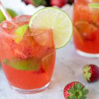 Glass of Strawberry Lime Water with strawberries and second glass behind