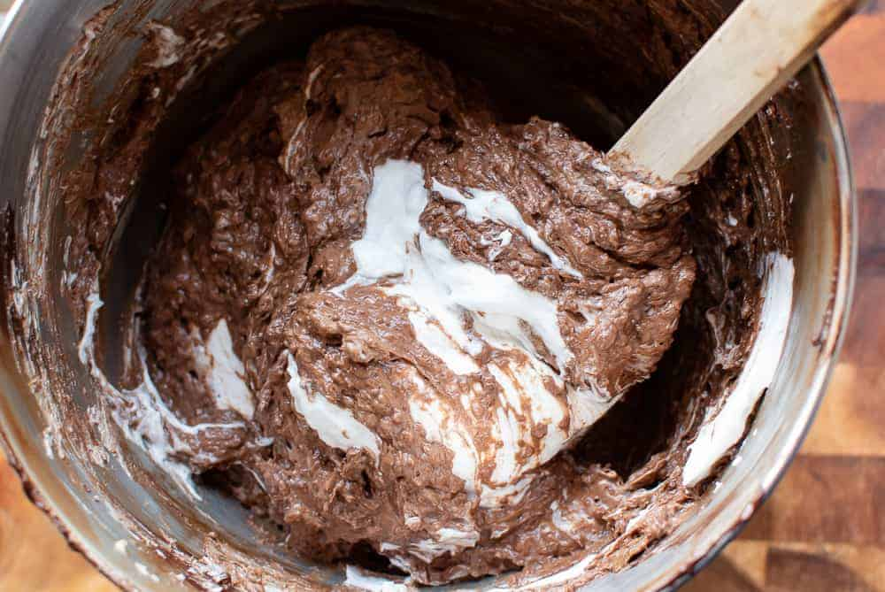 Chocolate almond cake batter and eggwhite being mixed