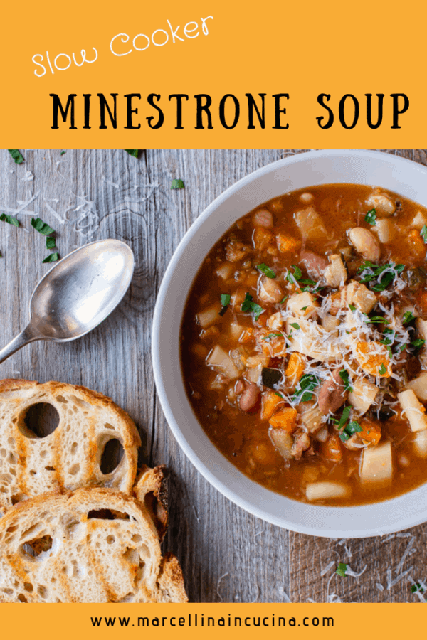 White bowl of slow cooker minestrone soup, two slices of toasted bread and spoon on wooden table